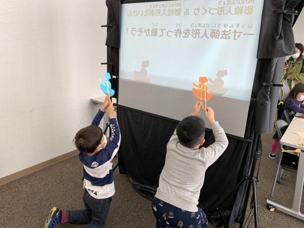 「おうちでできる!影絵人形の作り方」を伝えています。子供たちは手作り影絵人形(一寸法師)に夢中です。